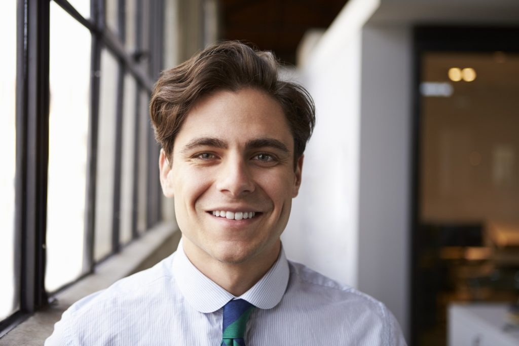 Young white businessman smiling to camera, portrait