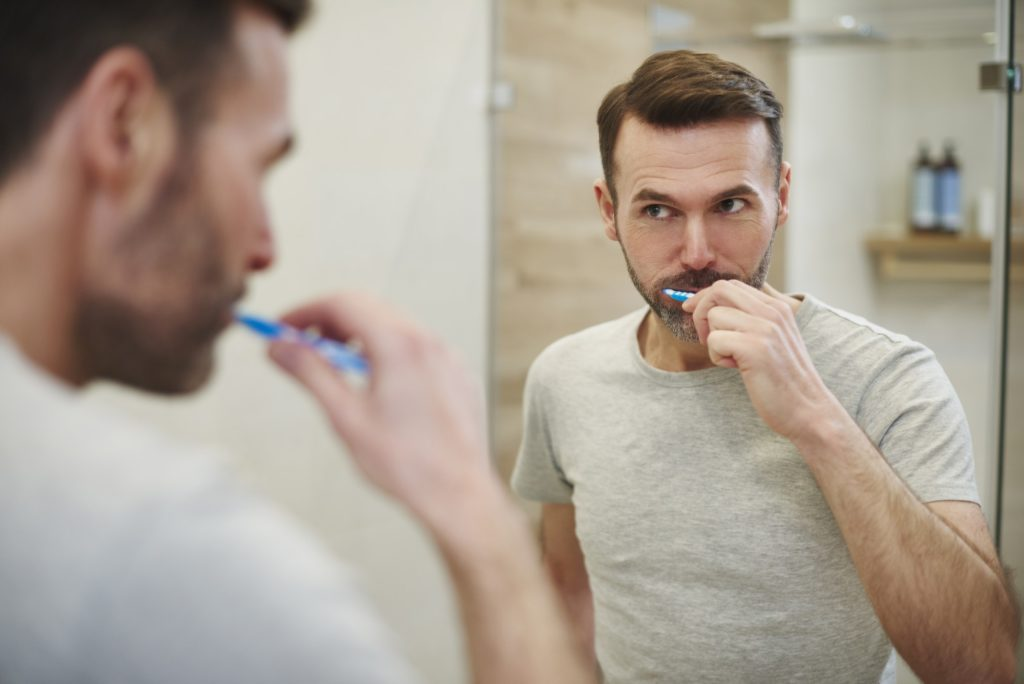 Man cleaning teeth in bathroom