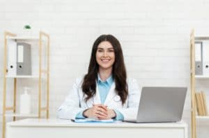 Friendly smiling millennial woman doctor sitting at desk at working place with laptop and smiling at
